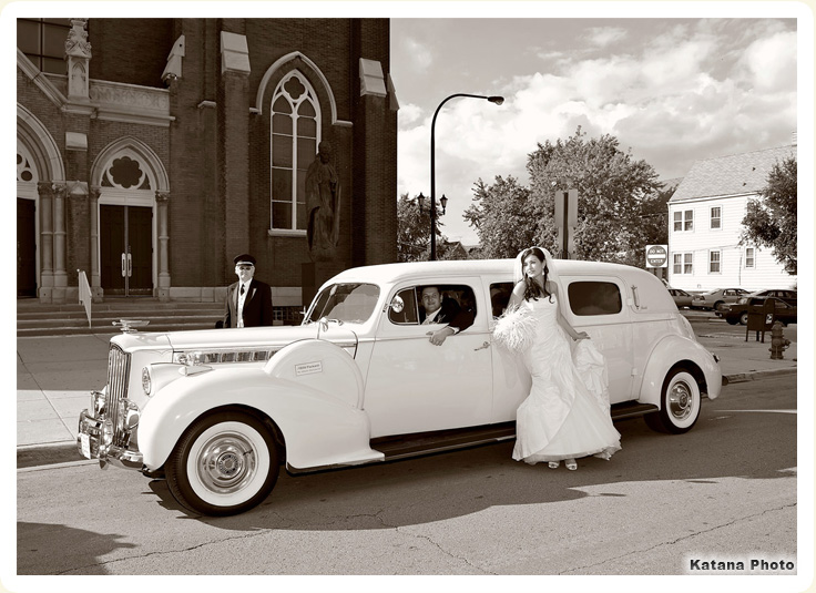 Luxury 1939 white packard photo showing groom driving with bride